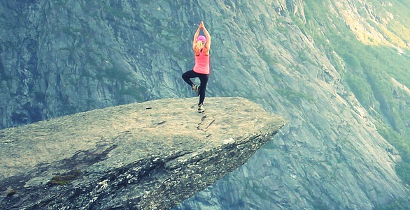 Lady balancing on the edge of cliff